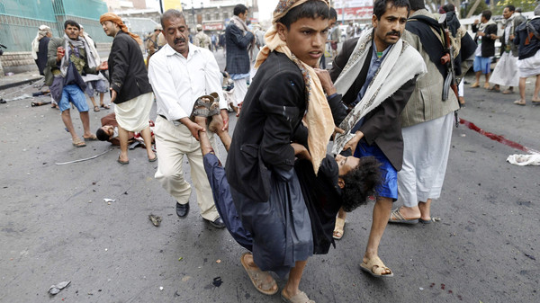 Shiite Houthi rebels carry a wounded man at the scene of a suicide attack in Sanaa October 9, 2014.