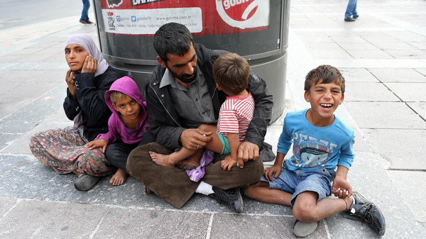 A family of Syrian refugees sits on Kizilay Square in downtown Ankara on October 13, 2014.
