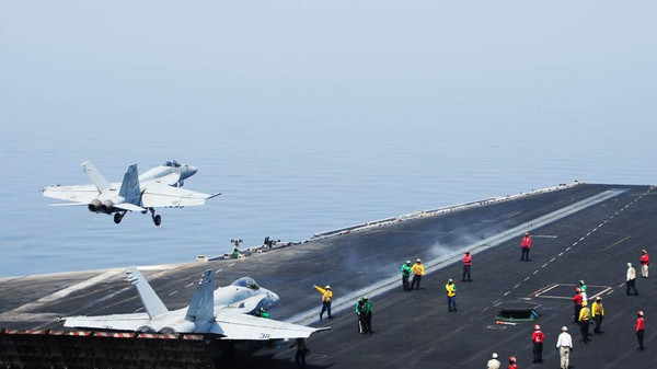 This U.S. Navy photo obtained August 8, 2014 shows sailors directing aircraft, as an F/A-18E Super Hornet takes off from the aircraft USS George H.W. Bush in the Gulf.