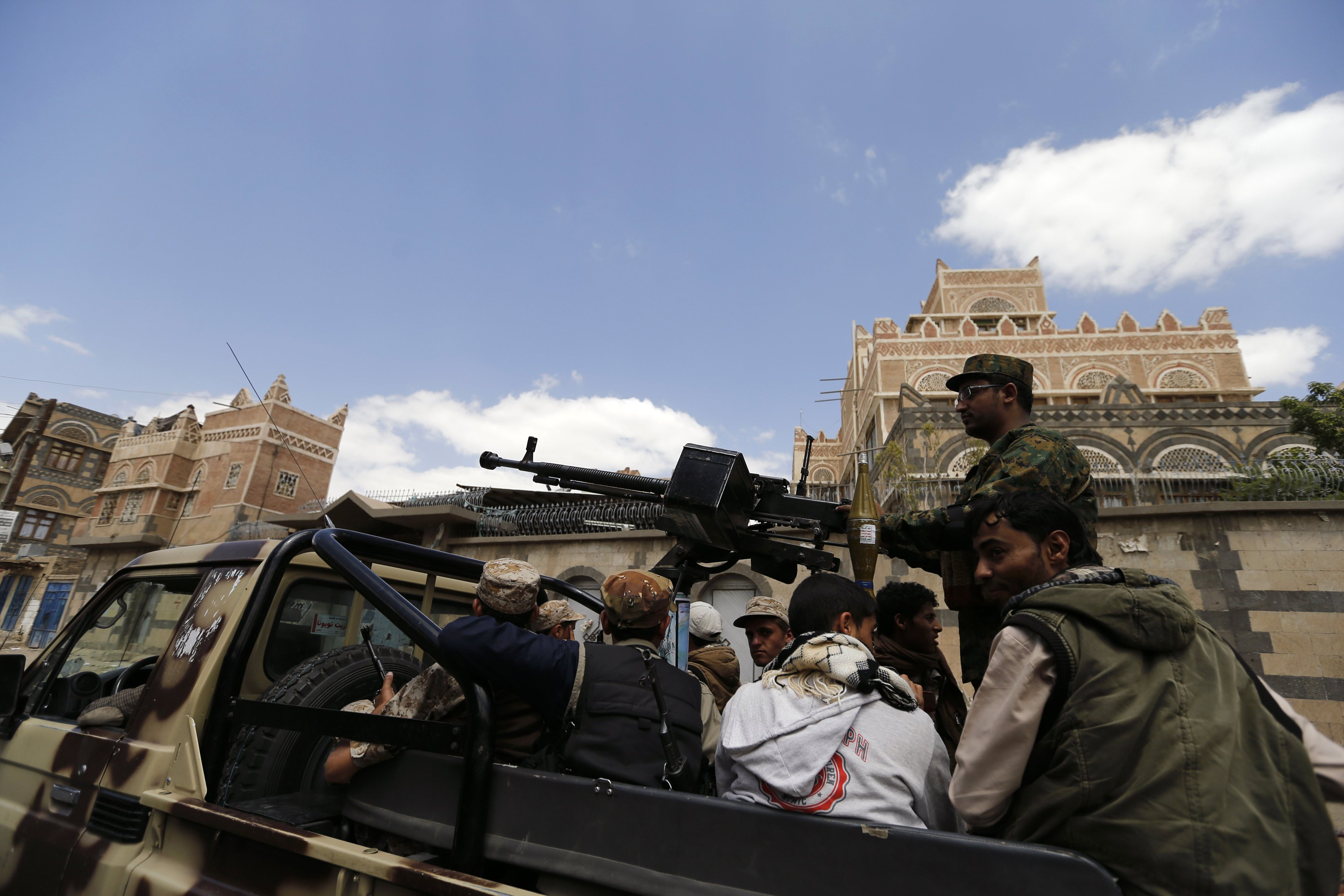 Shi'ite Houthi militants patrol the vicinity of a venue where a mass funeral for victims of a suicide attack on followers of the Shi'ite Houthi group was being held in Sanaa