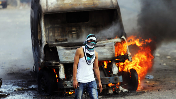 A Palestinian protester stands in front of a car of an Israeli that was set on fire by the protesters during clashes with Israeli security forces in east Jerusalem October 30, 2014.