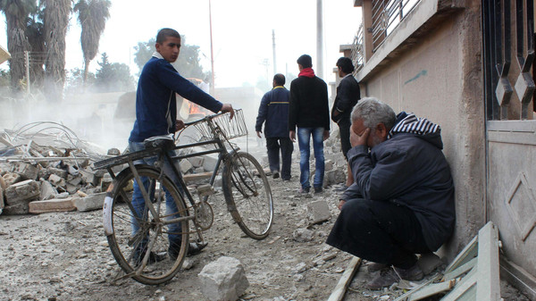 A Syrian man reacts following reported airstrikes by government forces in the Syrian city of Raqqa, a stronghold of the Islamic State of Iraq and Syria (ISIS), on Nov. 27, 2014.