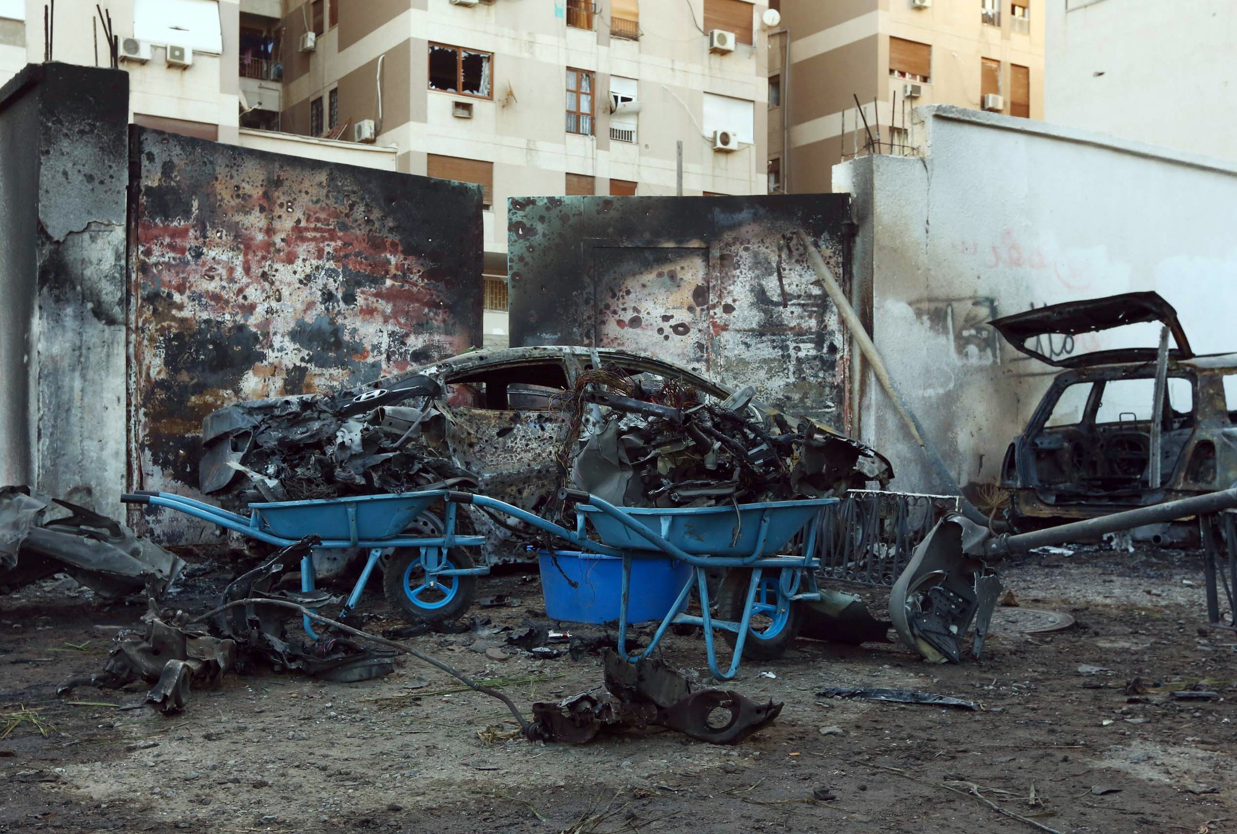 A destroyed vehicle is seen near the compound of the Egyptian embassy in the Libyan capital Tripoli on November 13, 2014 after it was targeted by a car bomb explosion.