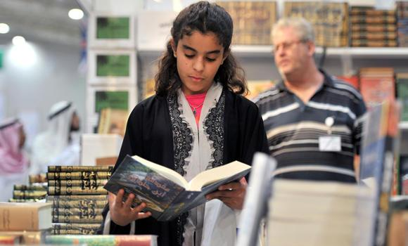 A girl reads a book at the Riyadh book fair. (SPA)