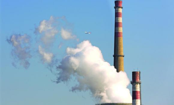 A passenger airliner flies past smokes emitted from a coal-fired power plant.