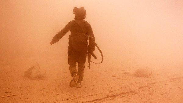 A rebel fighter runs through dust towards an area damaged by what activists said were barrel bombs dropped by warplanes loyal to Syria's President Bashar al-Assad, in Aleppo's al-Shaar neighborhood November 6, 2014.