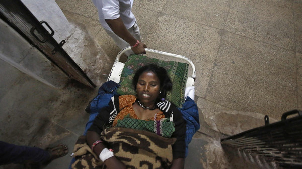 A woman, who underwent a sterilisation surgery at a government mass sterilisation camp, lies on a stretcher as she is taken to a hospital in Bilaspur, in the eastern Indian state of Chhattisgarh November 14, 2014.
