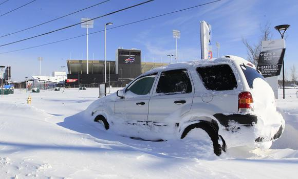 A car is abandoned in front of a snow covered Ralph Wilson Stadium home of the Buffalo Bills in Orchard Park, N.Y. on Nov. 19, 2014.