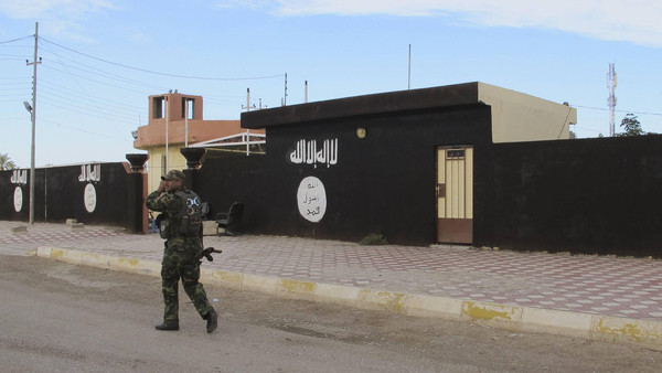 An Iraqi Shiite fighter walks past walls painted with the Islamist State flag, after Shiite fighters and Iraqi security forces took control of Saadiya in Diyala province from ISIS, November 24, 2014.