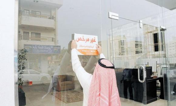 An SCTA official pastes a closure notice on the glass front of a hotel in Dammam.