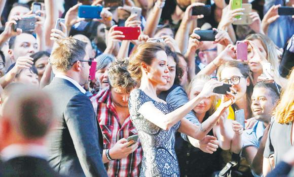 "Angelina Jolie takes a 'selfie' with fans at the world premiere of her film ""Unbroken"" at the State Theater in Sydney, on Monday."