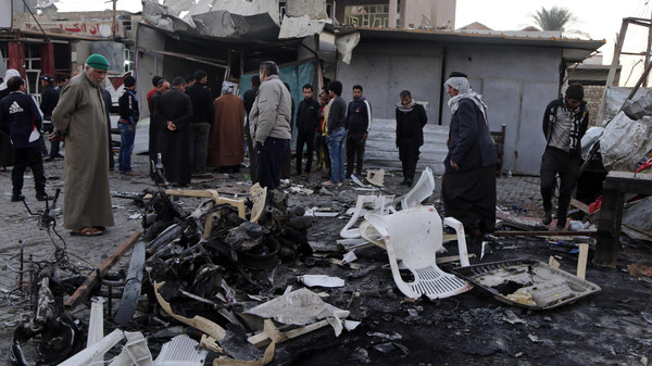 People gather at the site of a car bomb attack in Baghdad's Sadr City, November 9, 2014.