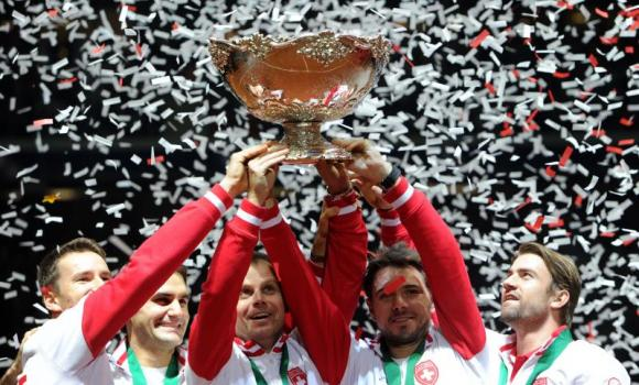 From left, Switzerland's Marco Chiudinelli, Roger Federer, Davis Cup team captain Severin Luthi, Stanislas Wawrinka and Michael Lammer celebrate with the trophy after winning the Davis Cup final between France and Switzerland at Stade Pierre Mauroy in Villeneuve-d'Ascq, northern France, on Sunday. Federer gave Switzerland its first Davis Cup title by defeating France's Richard Gasquet in straight sets in the first of the final's reverse singles.