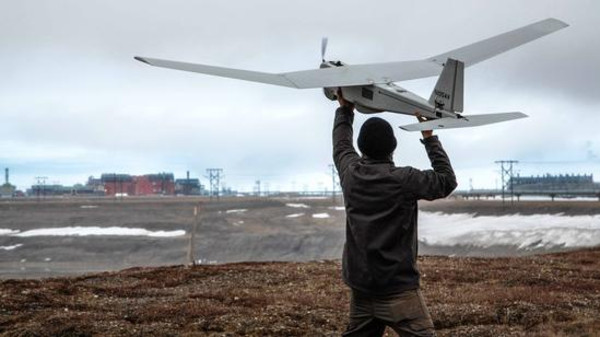 A man inspects a drone before launching it in Alaska, U.S.