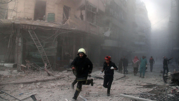 Emergency responders rush following a reported barrel bomb attack by government forces in the Al-Muasalat area in the northern Syrian city of Aleppo on November 6, 2014.