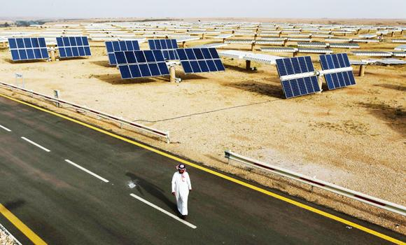 A Saudi man walks on a street past a field of solar panels at the King Abdulaziz city of Sciences and Technology, Al-Oyeynah Research Station in this May 21, 2012 file photo.