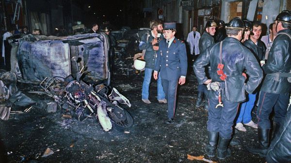 A file picture taken on October 3, 1980 shows firefighters standing by the wrekage of a car and motocycle after a bomb attack at a Paris synagogue on Rue Copernic which killed four people.
