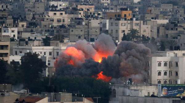 Flames erupt from a building hit by an Israeli air strike on July 9, 2014 in Gaza City.
