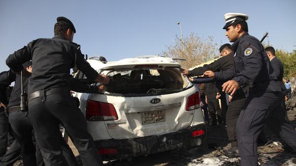 Kurdish security forces inspect the site of a car bomb attack in Arbil, the capital of Iraq's Kurdistan region ,Nov. 19, 2014.