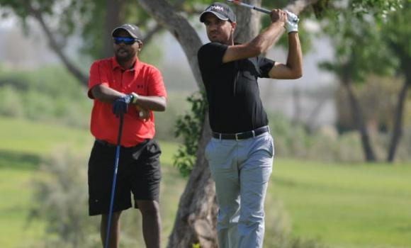 Othman Almulla in action during the SAIT at Rolling Hills Golf Club in Dhahran. Looking on is Bahrain's Sultan Abdullah.
