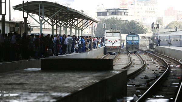 Passengers wait for their train near a damaged train carriage after a bomb exploded at Ramsis railway station in downtown Cairo November 20, 2014.
