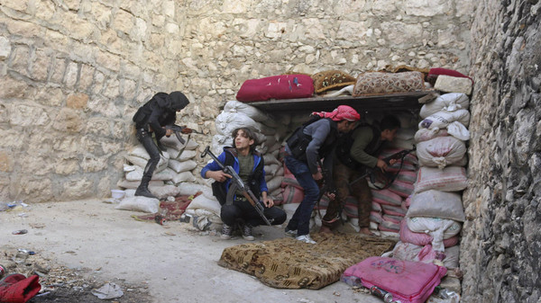 Rebel fighters take up position behind piles of sandbags on the Karm al-Tarab frontline, next to Aleppo International airport November 23, 2014.