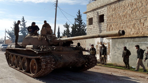 Rebel fighters drive a tank on the road between the villages of Zahraa and Nubol in the northern Syrian Aleppo province during clashes with pro-government fighters on Nov. 23, 2014.
