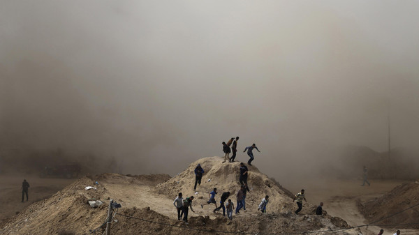 Palestinians run as smoke rises after a house is blown up on the border of the southern Gaza Strip.