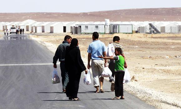 Syrian refugees carry bags after collecting food from a supermarket at a refugee camp that opened in Azraq, in the Jordanian eastern desert, some 100 kilometres east of Amman, in this April 30, 2014 photo, on its opening day.
