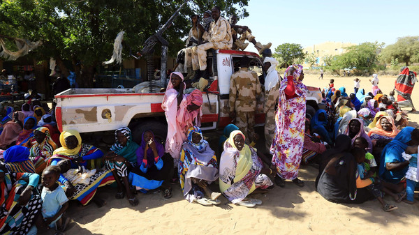 Women sit near a vehicle of the special police forces after it arrived in Tabit village in North Darfur Nov. 20, 2014. UNAMID has been trying to gain access to visit Tabit since earlier this month to investigate media reports of an alleged mass rape of 200 women and girls there.