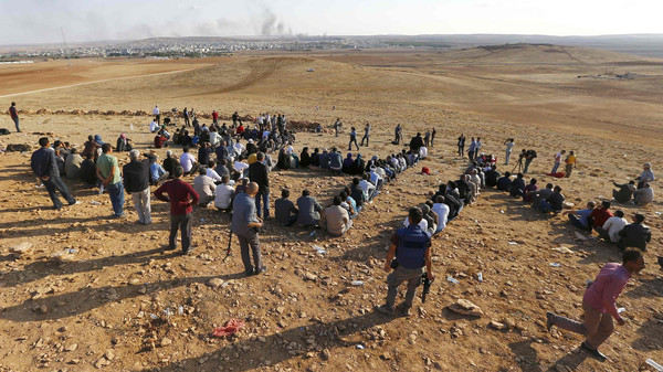 Turkish Kurds gather on the hill near the Mursitpinar border crossing on the Turkish-Syrian border near the southeastern town of Suruc in Sanliurfa province to support Kurdish fighters in Kobane.