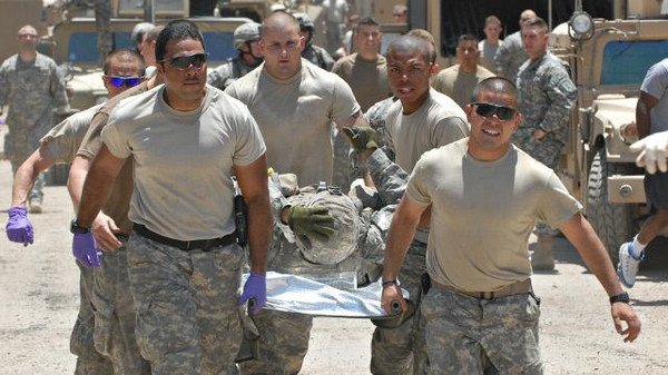 Soldiers at a forward operating base Apache in eastern Baghdad carry injured soldiers to the medical center after an IED destroyed a Bradley fighting vehicle killing five US soldiers and an Iraqi interpreter in 2007.