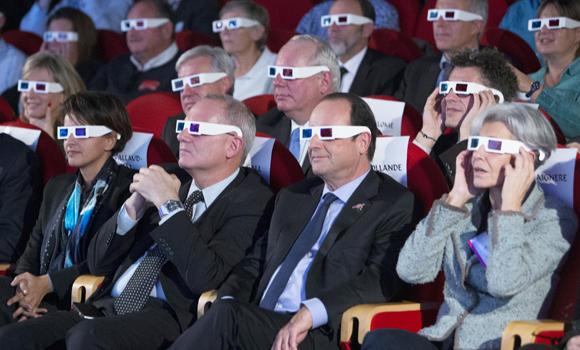 French National Center for Space Studies (CNES) president Jean-Yves Le Gall, second left, French President Francois Hollande, center, and former French minister and astronaut Claudie Haignere, right, wear 3D glasses as they visit the Cite des Sciences at La Villette during a broadcast of the Rosetta mission as it orbits around comet 67/P Churyumov-Gersimenko in Paris on Nov. 12, 2014.