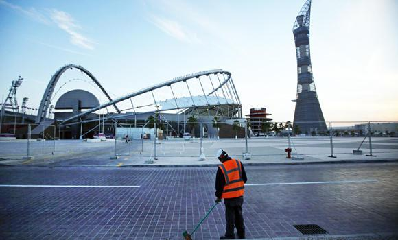 A worker cleans the road outside Khalifa sport complex in Doha, Qatar.
