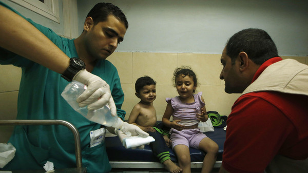 Palestinian children, who hospital officials said were wounded in an Israeli air strike, receive treatment at a hospital in Gaza City in August.