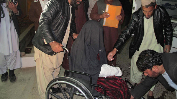 A wounded Afghan woman (C) is brought to the hospital in Helmand province early on Jan. 1, 2015 after a rocket fired during fighting between Afghan forces and insurgents killed at least 15 wedding guests late on Dec. 31.