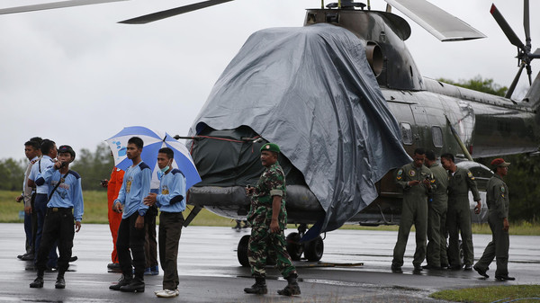 An Indonesian military helicopter, used in recovery efforts for the missing AirAsia plane, sits idle on the tarmac at Iskandar Airport during bad weather in Pangkalan Bun, Central Kalimantan, Dec. 31, 2014.