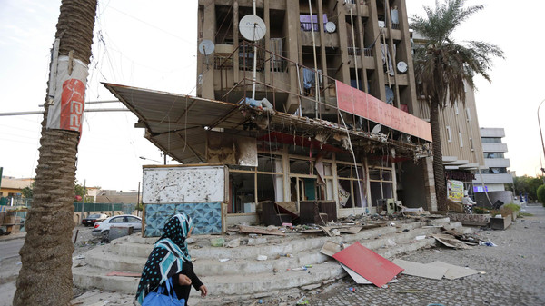 A woman walks past the site of a car bomb attack in Baghdad, Oct. 18, 2014.