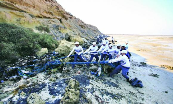Hadeed employees work on a pile of trash during the clean-up campaign on Jinnah Island in Jubail.