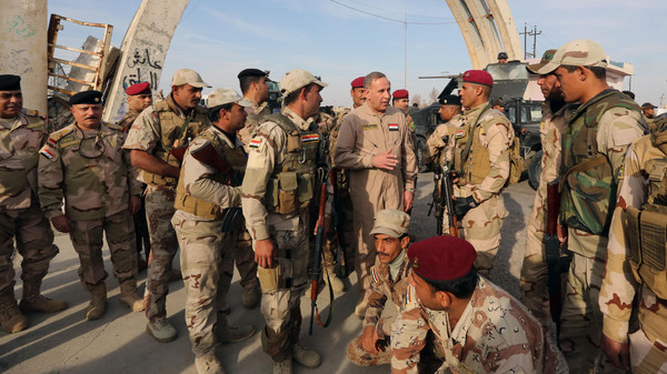Iraqi Defense Minister Khalid al-Obeidi, center, speaks to his soldiers after a military operation to regain control of the university of Tikrit, 130 kilometers north of Baghdad, Iraq in 2014.