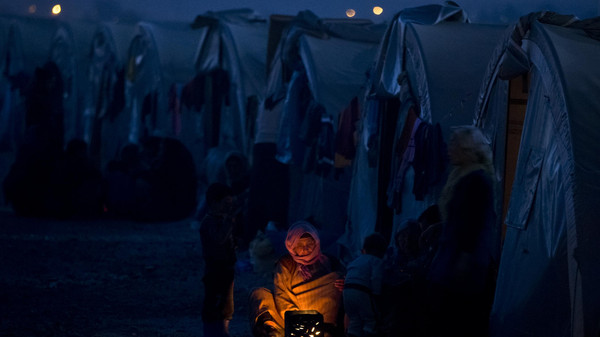 An elderly Syrian Kurdish refugee woman from the Kobane area, warms up by a fire at a camp in Suruc, on the Turkey-Syria border Monday, Nov. 10, 2014.