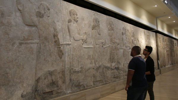 Visitors look at Assyrian mural sculptures from Khorsabad, at the Iraqi National Museum in Baghdad March 8, 2015.
