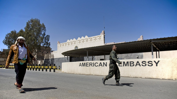 Houthi Yemenis walk past the gate of the main entrance of the closed U.S. embassy after Yemeni police opened the road in front of it, in Sanaa, Yemen, March 4, 2015.