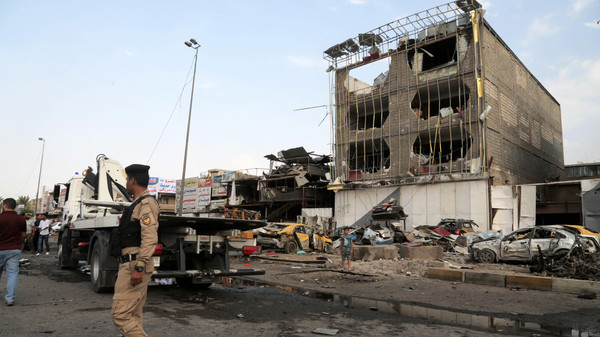 Security forces inspect the site of a car bomb explosion in the largely Shiite eastern neighborhood of Talibiyah in Baghdad, Iraq, Oct. 16, 2014.