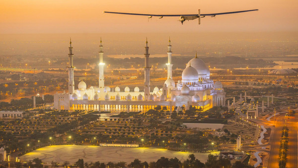 The Solar Impulse 2, a solar-powered plane, flies over the Sheikh Zayed Grand Mosque in Abu Dhabi during preparations for next month's round-the-world flight, February 26, 2015.