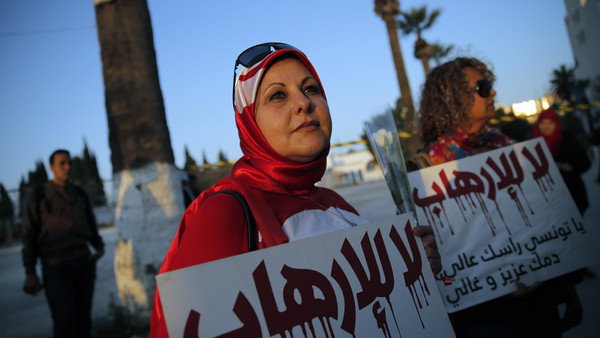 "A woman holds a placard reading: ""No to Terrorism"" as she demonstrates in front of the National Bardo Museum a day after gunmen attacked the museum and killed scores of people in Tunis, Tunisia, Thursday, March 19, 2015. The Islamic State group issued a statement Thursday claiming responsibility for the deadly attack on Tunisia's national museum that killed scores of people, mostly tourists."