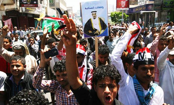 Yemenis hold a poster of the King of Saudi Arabia Salman as they chant slogans during a rally to show support for Saudi-led airstrikes against Shiite rebels, known as Houthis, in Taiz, Yemen, on Thursday.