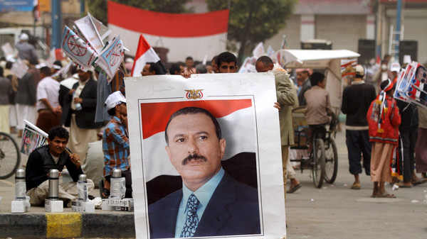 A supporter of Yemen's former president Saleh holds up his portrait during a rally.