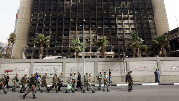 Army soldiers march in front of the burned down building of Hosni Mubarak's National Democratic Party in Cairo.