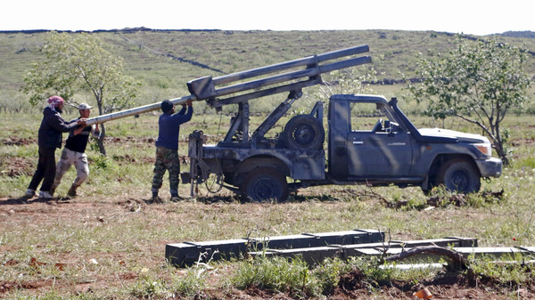 Rebel fighters from the Ahrar al-Sham Islamic Movement prepare to fire grad rockets from Idlib countryside towards forces loyal to Syria's President Assad.